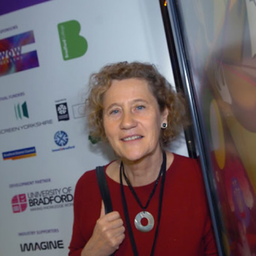 Portrait of Vivien Halas in front of logos