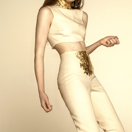 Model in high waisted white trousers and white cropped top with gold details and gold headpiece.
