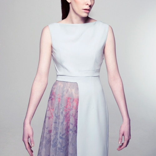 Female model in pale dress with half of the skirt patterned.
