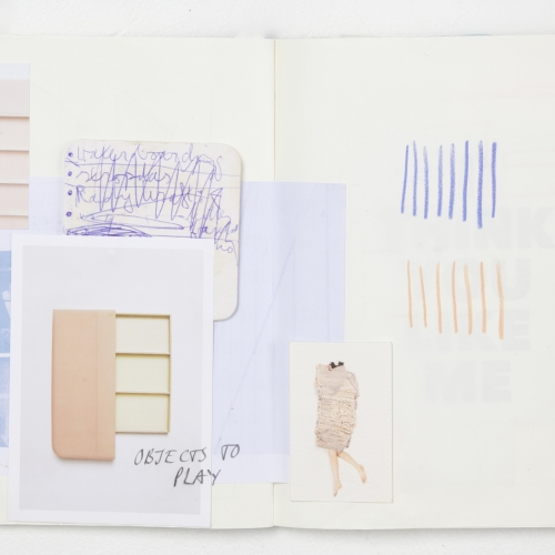 Open sketchbook, scribbles, photograph, pink and blue tones.