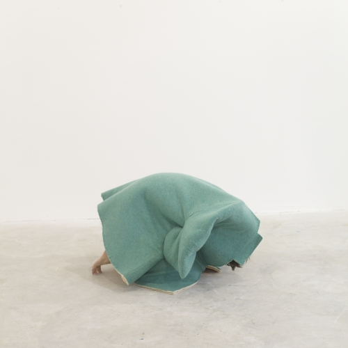 Obscured model curled up on floor covered by pale green outfit.