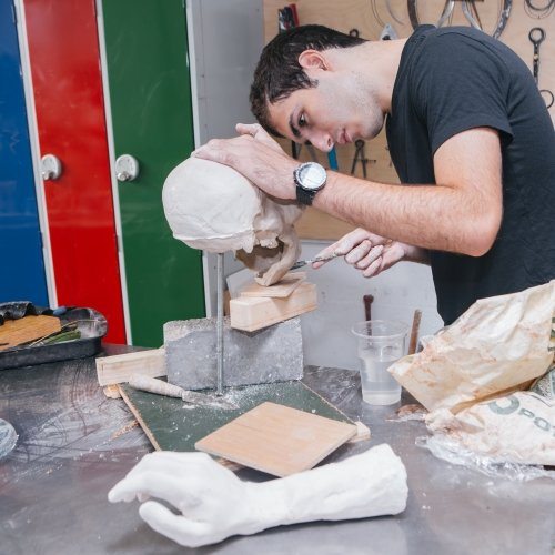 Male student working on a ceramic skull in workshop