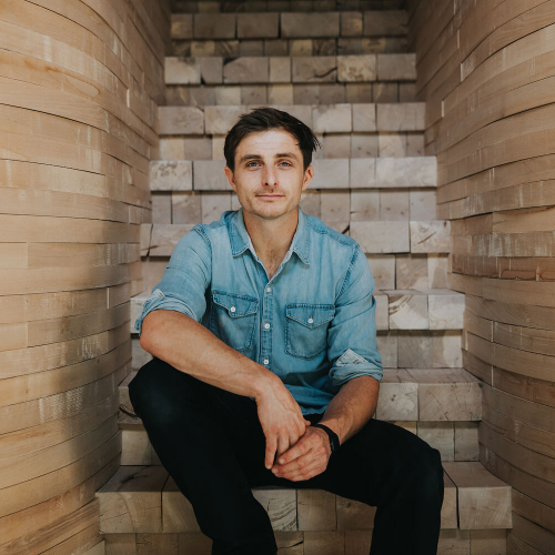 Falmouth University alumni Tom Raffield sitting on wooden steps