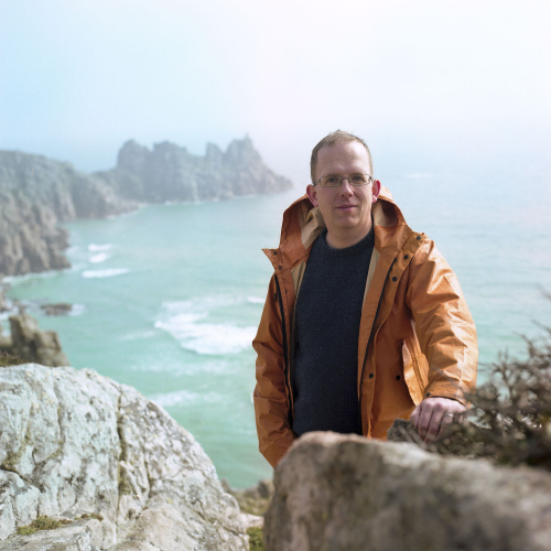 Writer, Wyl Menmuir, standing on cliff with sea view in the background.